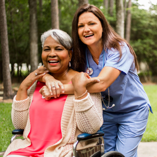 Elderly lady in wheelchair being hugged by nurse