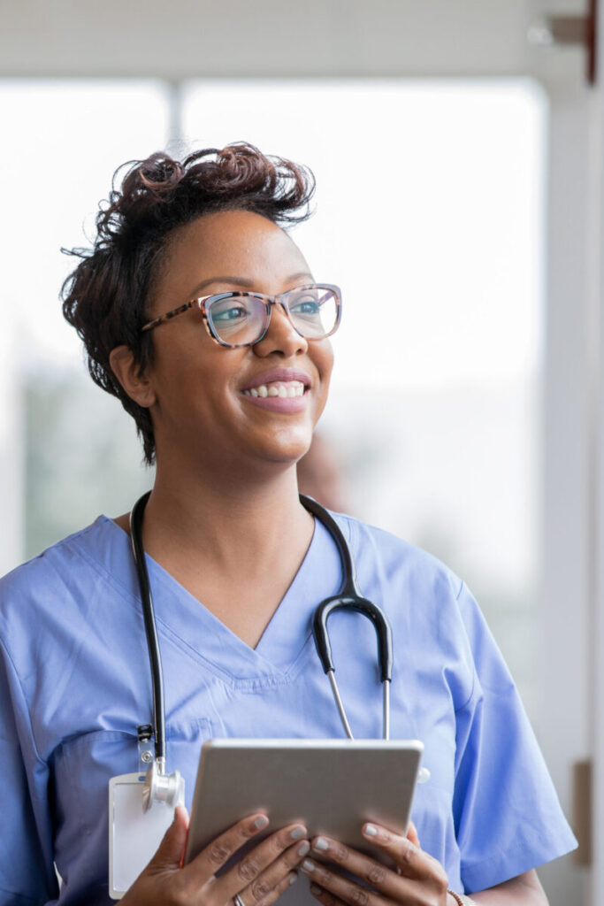 Beautiful nurse smiles while holding digital tablet