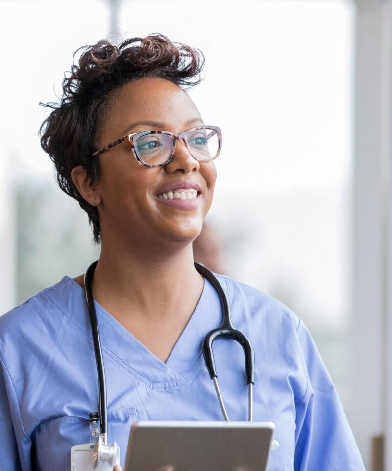 Beautiful nurse smiles while holding digital tablet